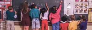 Children at school at blackboard