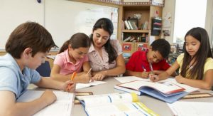 Teacher with children in classroom studying